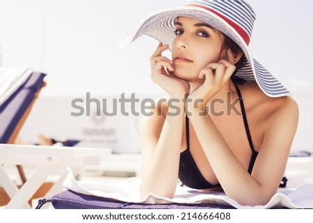 Beautiful brunette woman on the beach in pool alone relaxing in swimsuit and hat. Summer. Outdoors. copy space - stock photo