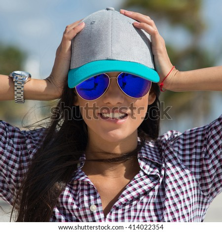 Beautiful brunette woman portrait wearing sunglasses and hat on a tropical beach in Miami, Florida. - stock photo