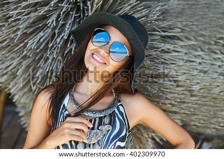 Beautiful brunette woman posing at sunny summer day close up portrait. Girl wearing fashionable sunglasses and hat - stock photo