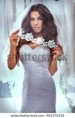 Beautiful brunette woman posing in fashionable white wedding dress. Studio shot. - stock photo