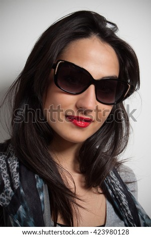 Beautiful brunette woman posing in studio on gray background with sunglasses ..
