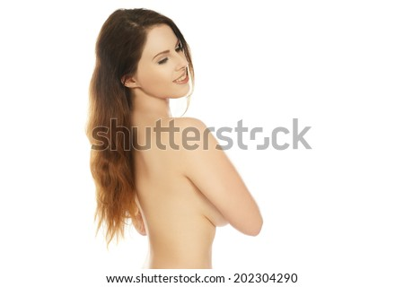 Beautiful brunette woman posing topless sideways to the camera with her arm concealing her breast turning to smile over her shoulder, upper body portrait on white
