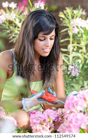 Beautiful brunette woman pruning flowers and smiling in garden - stock photo