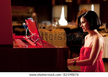 beautiful brunette woman red dress playing piano - stock photo
