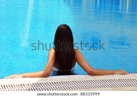 Beautiful brunette woman relaxing in a swimming pool - stock photo