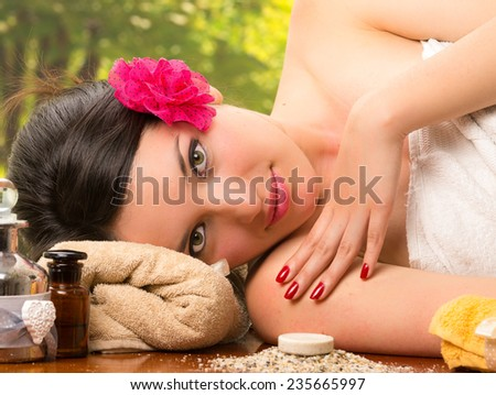 beautiful brunette woman relaxing lying down in outdoor spa