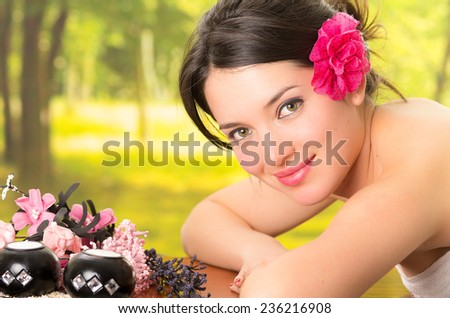 beautiful brunette woman relaxing lying down in outdoor spa - stock photo