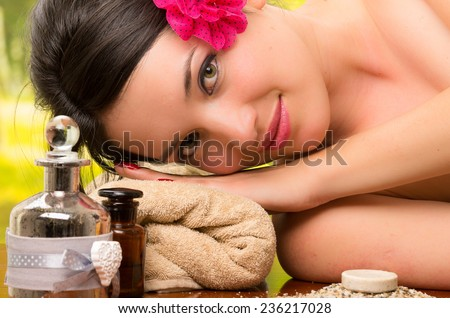 beautiful brunette woman relaxing lying down smiling in outdoor spa