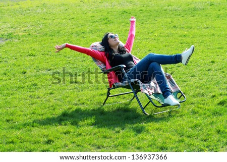 beautiful brunette woman relaxing on lounger in the spring grass