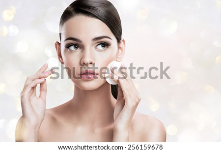Beautiful brunette woman removing makeup from her face, skin care concept / photoset of attractive brunette girl on blurred background with bokeh  - stock photo