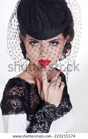 Beautiful Brunette Woman. Retro Fashion portrait in elegant hat with red lips and manicured nails. - stock photo