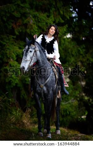 beautiful brunette woman riding horse - stock photo