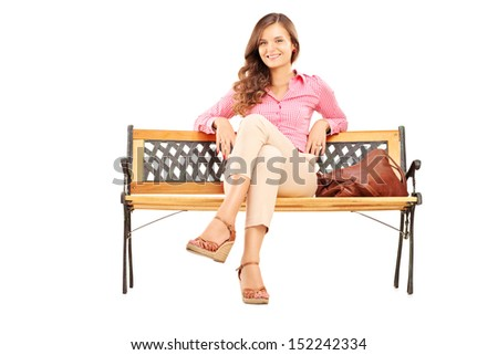 Beautiful brunette woman sitting on a wooden bench and looking at camera isolated on white background - stock photo