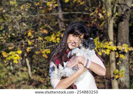 beautiful brunette woman smiling and hugging her little cute white dog in the autumn park