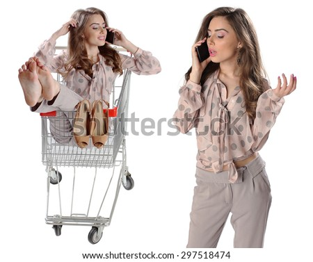 Beautiful brunette woman talking on mobile phone sitting in an empty shopping trolley, isolated on white background - stock photo