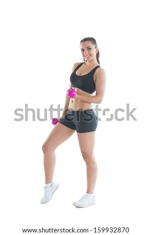 Beautiful brunette woman training her arms with dumbbells smiling at camera - stock photo