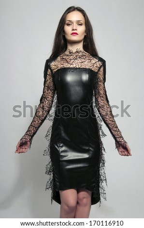 Beautiful brunette woman wearing a black dress and looking evil - stock photo