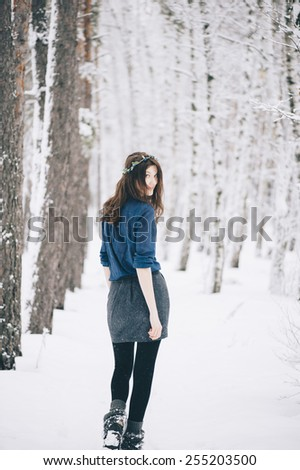 Beautiful brunette woman wearing a wreath turning back to the camera in the winter snowy forest - stock photo