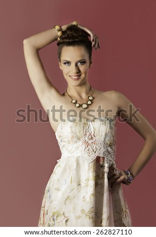 Beautiful brunette woman wearing floral dress and spring makeup, posing with her hand on her hip and the other over her head in front of a bright pink background