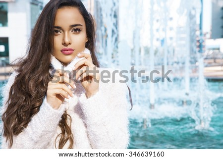 Beautiful  brunette woman wearing knitted sweater and standing in front of fountain. Fall and winter fashion concept. Horizontal shot, outdoors - stock photo