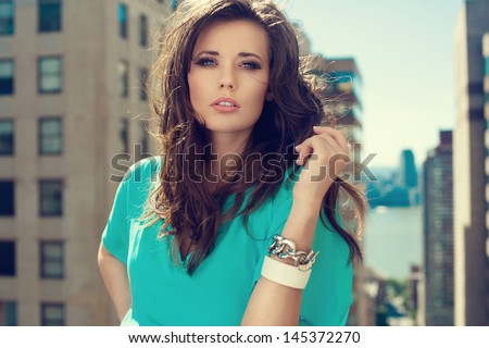 Beautiful brunette woman wearing loose dress standing on the rooftop  - stock photo