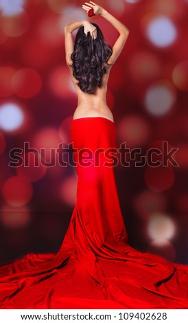 Beautiful brunette woman wearing red dress. Fashion photo in studio.
