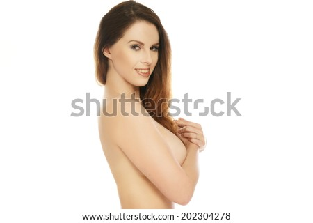 Beautiful brunette woman with a lovely smile posing topless with her long hair cascading over her breast which she is concealing with her hand, isolated on white