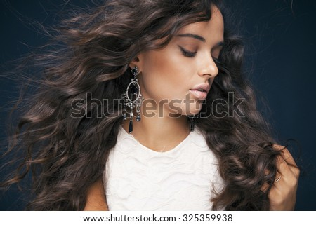 Beautiful brunette woman with beauty long curly hair and bright makeup. Fashion model with wavy hairstyle. Toned in warm colors. Studio shot, horizontal - stock photo