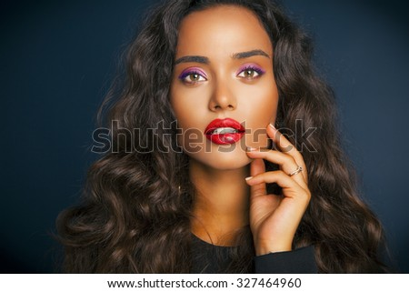 Beautiful brunette woman with beauty long curly hair and colorful makeup. Red Lips. Fashion model with wavy hairstyle. Toned in warm colors. Studio shot, horizontal  - stock photo