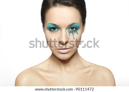 Beautiful brunette woman with black eyes and blue bright colorful makeup closeup portrait isolated on white - stock photo