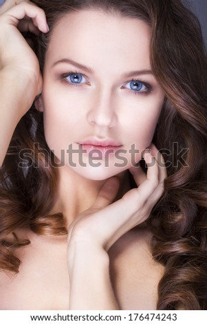 Beautiful brunette woman with blue eyes without make up, natural flawless skin and hands near her face