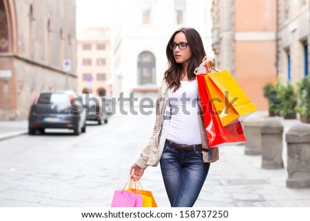 Beautiful brunette woman with brown glasses carrying shopping bags in city street - outdoor portrait - stock photo