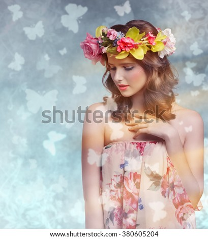 Beautiful, brunette woman with colorful makeup, wreath of flowers on head, very colorful image