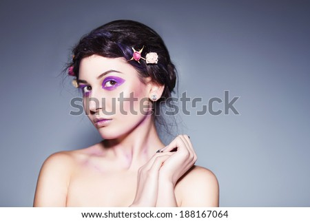 Beautiful brunette woman with creative make up and dead roses in braid hairstyle - stock photo