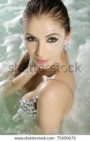 beautiful brunette woman with diamond make up in swimmingpool - stock photo