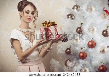 beautiful brunette woman with elegant fashion outfit, pearl necklace, hair-style and cute make-up taking christmas present in the hand near decorated xmas tree