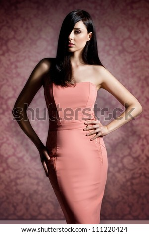 beautiful brunette woman with elegant hairstyle wearing nice coral evening dress - stock photo