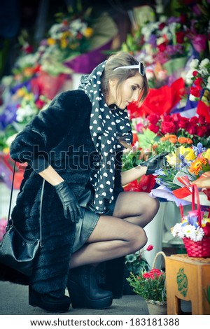Beautiful brunette woman with gloves choosing flowers at the florist shop. Fashionable female with sunglasses and head scarf at flower shop. Pretty brunette in black choosing flowers - urban shot - stock photo