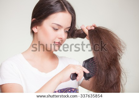 Beautiful brunette woman with hairbrush