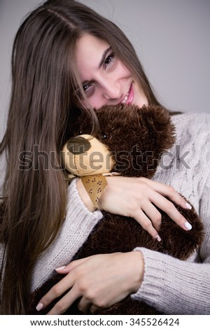 Beautiful brunette woman with her teddy bear. Color effects and custom white balance are used on this picture. - stock photo