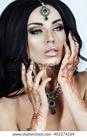 Beautiful Brunette Woman With Indian Jewelry Glamour Style. Curly Hairstyle. Bright Makeup. Sexy Lips