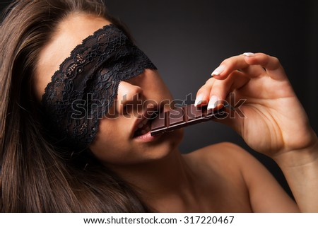 Beautiful brunette woman with lace on eyes, eating chocolate.