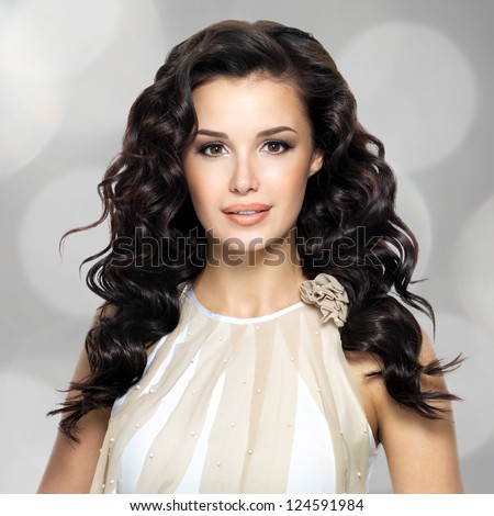 Beautiful brunette woman with long curly hairstyle. Portrait of a fashion model. Blinking Background. Bokeh - stock photo