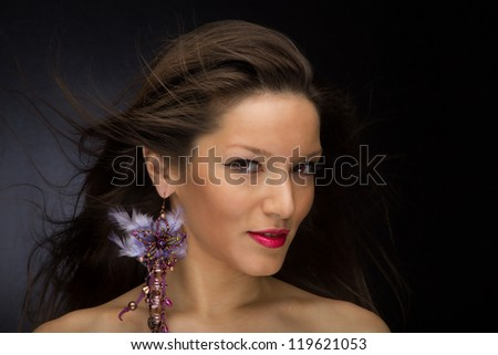 Beautiful Brunette woman with Long Hair over dark background