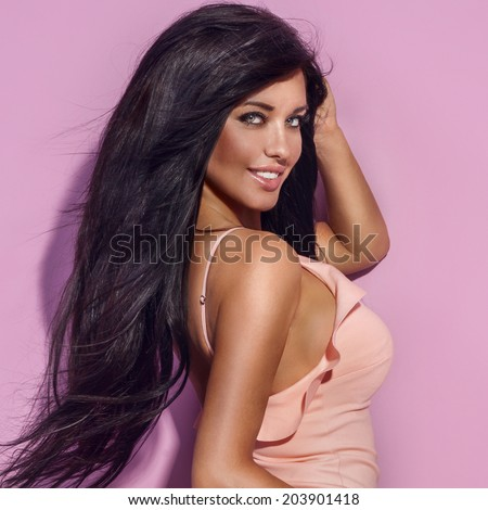Beautiful brunette woman with long healthy brunette hair and amazing toothy smile looking at camera. - stock photo