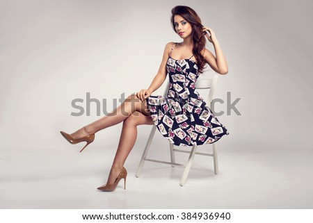 Beautiful brunette woman with lovely long hair posing in a sexy summer dress, sunglasses  in a studio. Fashion photo