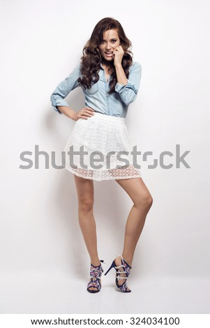 Beautiful brunette woman with lovely long hair posing in a sexy white skirt and jeans shirt in a studio. Fashion photo - stock photo