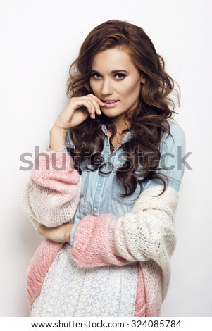 Beautiful brunette woman with lovely long hair posing in jeans shirt and sweater in a studio. Fashion photo - stock photo