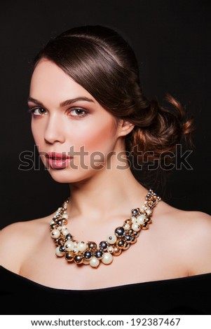 beautiful brunette woman with perfect makeup wearing jewelry