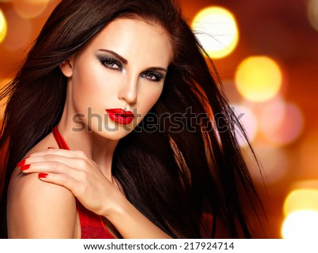 Beautiful brunette woman with red lips and nails.  Face of a pretty girl over night lights  background - stock photo